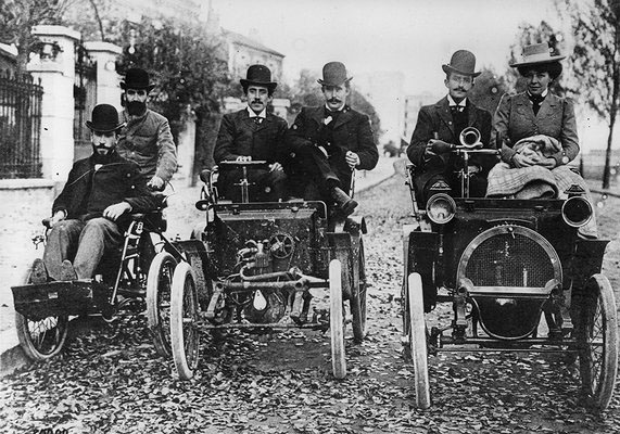 Sur le quai de Seine, Fernand et Marcel Renault sur le tricycle De Dion, et Louis Renault au volant du prototype de voiturette © Renault Histoire.