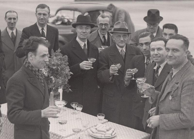 Charles-Edmond Serre au centre, légèrement à droite, avec des lunettes, boit le champagne pour célébrer à Montléry le succès des 50 heures, pied au plancher de la Juvaquatre, le 28 mars 1938 : 5931 Km parcourus à 107,82 Km de moyenne. A sa droite, J.A Grégoire et le groupe des pilotes Massot, Quatresous, Fromentin ; à sa gauche, Hamberger © Jacqueline Serre - Tous droits réservés